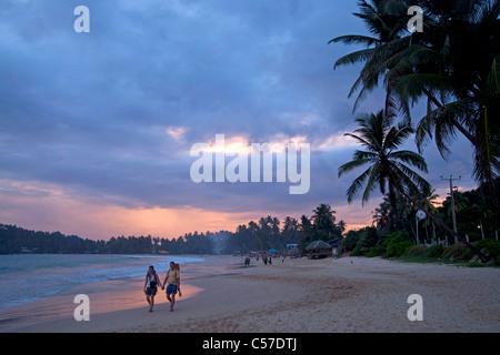 sunset walk at he beach Mirissa, Sri Lanka - Stock Photo