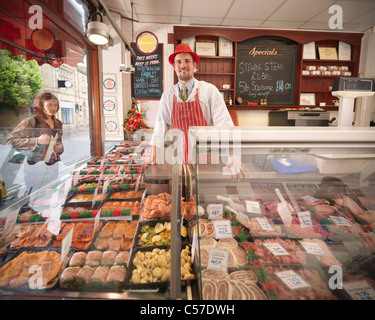 Butcher standing behind counter in shop - Stock Photo