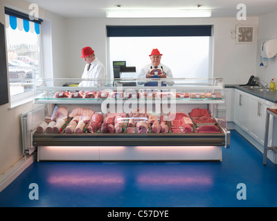Butcher standing behind meat counter - Stock Photo