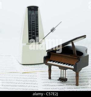 Metronome and miniature piano on the score - Stock Photo