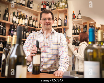 Wine merchant with bottle in shop - Stock Photo