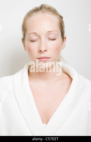 Woman wearing bathrobe with eyes closed - Stock Photo
