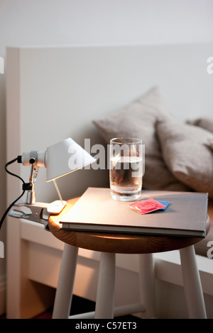 Condoms and water on bedside table - Stock Photo