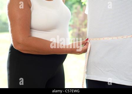 Woman measuring man's waist - Stock Photo