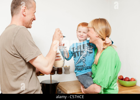 Parents feeding reluctant son in kitchen - Stock Photo