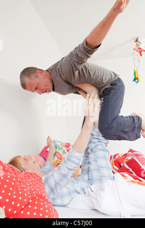 Smiling couple playing in bed together - Stock Photo