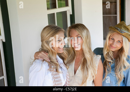 Mother and daughters standing on porch - Stock Photo