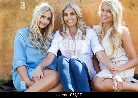 Mother and daughters sitting together - Stock Photo