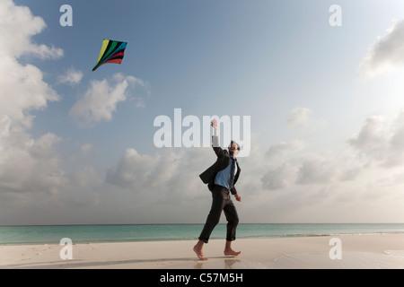 Businessman flying a kite on beach - Stock Photo