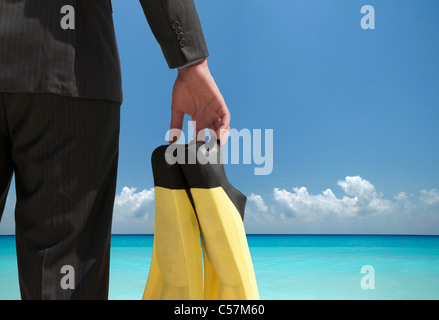Businessman carrying fins on beach - Stock Photo
