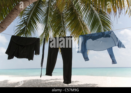 Business clothes drying on line on beach - Stock Photo