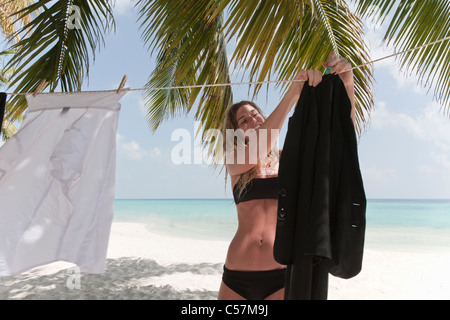 Woman hanging business clothes on beach - Stock Photo