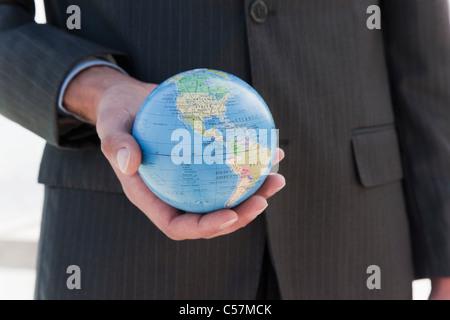 Businessman holding globe - Stock Photo