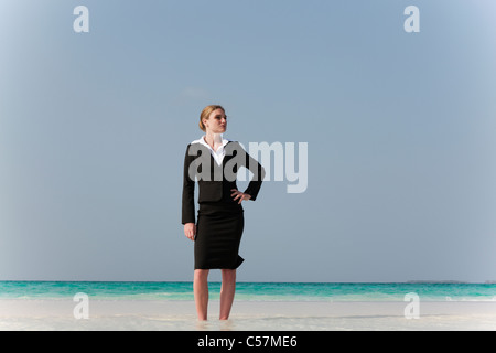 Businesswoman standing on tropical beach - Stock Photo