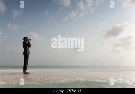 Businessman using binoculars on beach - Stock Photo