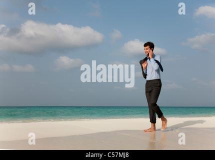 Businessman on cell phone on beach - Stock Photo