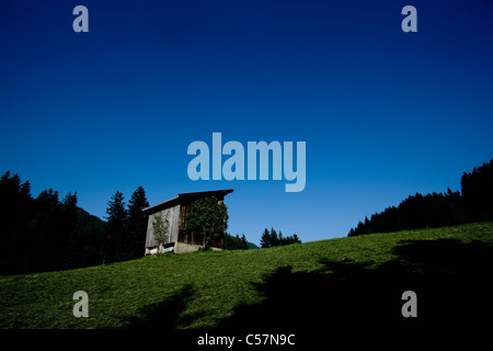 Shack on hillside against blue sky - Stock Photo
