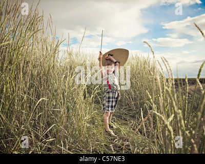 Boy playing with sword in wheat field - Stock Photo