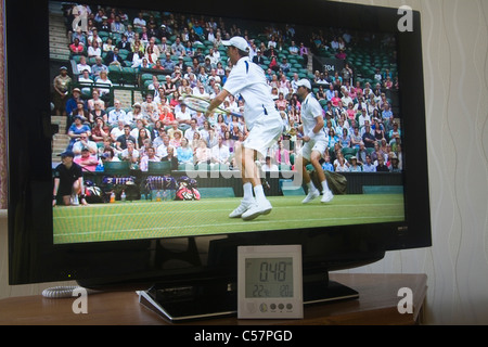 Owl electricity power usage monitor in front of a flat screen television set showing Wimbledon doubles tennis final - Stock Photo