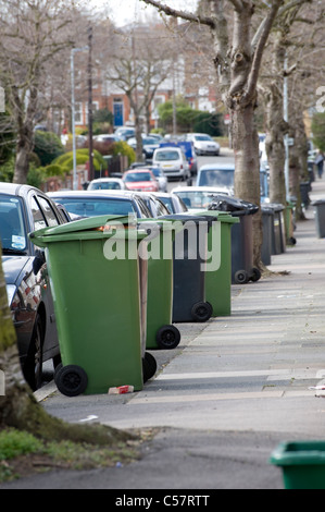 Wheelie bins containing household waste waiting for collection outside a house in England. - Stock Photo
