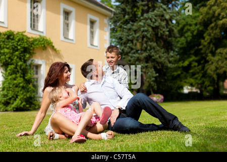 Young happy family sitting in the sun on the lawn in front of their new home - a villa - Stock Photo