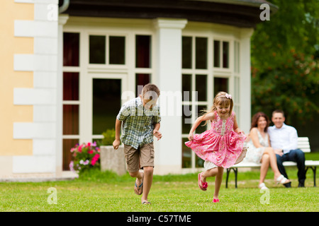Young happy family - the children are playing and the parents sitting in the sun on a bench in front of their villa - Stock Photo