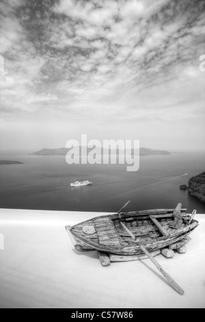 Thira on iconic Greek island of Santorini, typical Greece, old rotting wooden rowing boat on white washed building - Stock Photo