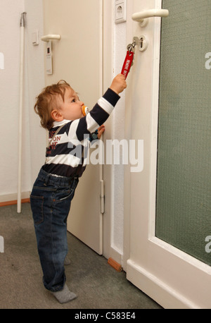 Little boy, one year old. At home. Exploring, trying to open a door. - Stock Photo