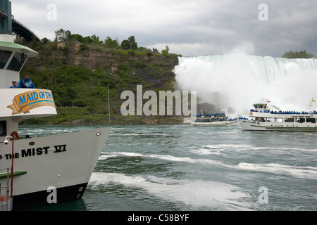 maid of the mist boats in dock and beneath the american side of niagara falls ontario canada - Stock Photo