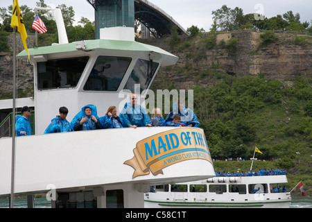 tourists in blue plastic waterproof ponchos boarding the upper deck of the maid of the mist niagara falls ontario - Stock Photo