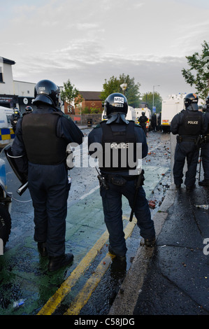 Police officers in riot gear at a riot - Stock Photo