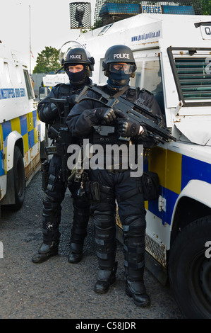 Police officers in riot gear at a riot armed with a Heckler & Koch G36C automatic machine gun stand beside an armoured - Stock Photo