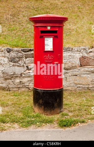 A red UK cast-iron Royal Mail freestanding Pillar Box with an EiiR Royal Cypher. - Stock Photo