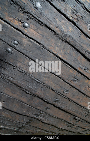 Hull boarding of an old wooden steam ship . Boards treated with tar against wear and pitch used to seal the slits - Stock Photo