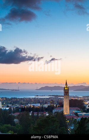 The Campanile (Sather Tower) of UC Berkeley aglow at sunset with the San Francisco Bay in the background. - Stock Photo