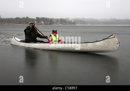 man and child sitting in a canoe on a frozen lake - Stock Photo