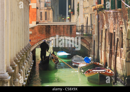 Gondola passing on small canal among old historic houses and bridge in Venice, Italy. - Stock Photo