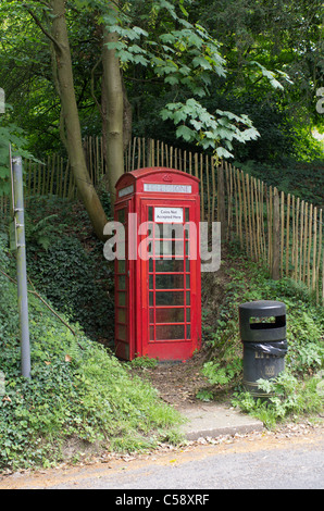 old style English telephone box iat Chiddingstone, Kent with a notice to tell potential vandals that the box does - Stock Photo