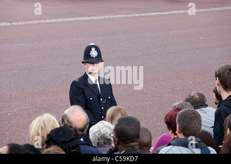 British policeman observes the crowd of spectators during the Trooping the Color ceremony in London, England on - Stock Photo