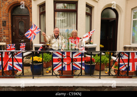 Two people waving flags in a garden decorated with Union Jacks at a street party - Stock Photo