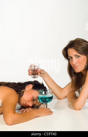 Woman after a few drinks too many being woken up by a friend - Stock Photo