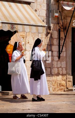 Two nuns enjoying ice cream cones on a hot afternoon in old Dubrovnik, Dalmatia Croatia - Stock Photo