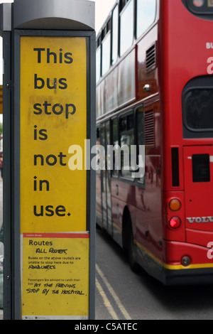 A bus passing a bus stop which is out of action due to nearby roadworks - Stock Photo