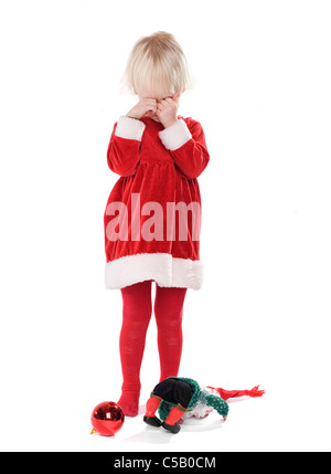 Little sad girl in Santa costume crying with toys on floor over white background - Stock Photo