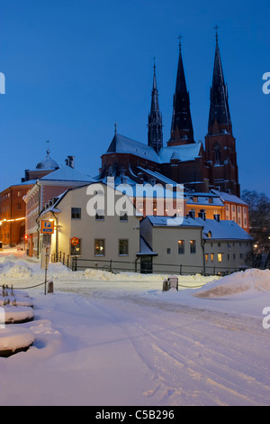 Snow covered roads with houses and cathedral in background against clear blue sky at Uppsala, Sweden - Stock Photo