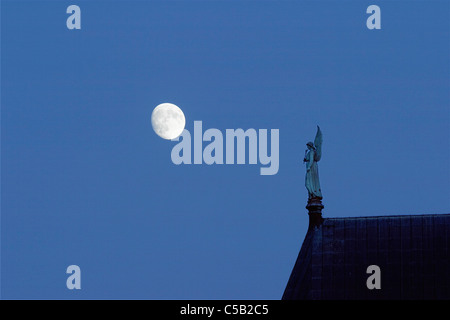 Full moon by the angel statue at the roof of Uppsala Cathedral against clear blue sky, Sweden - Stock Photo