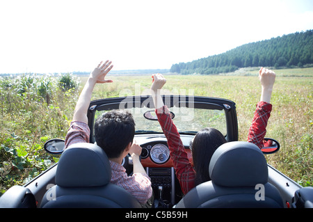Rear view of young couple riding in convertible car - Stock Photo