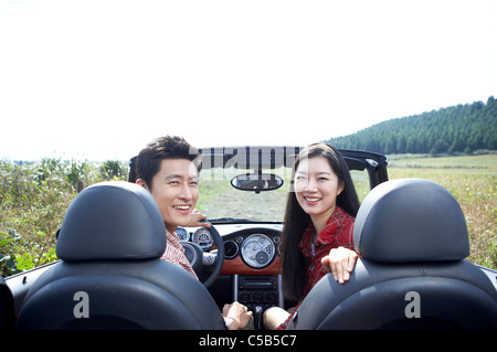 Portrait of young couple riding in convertible car - Stock Photo