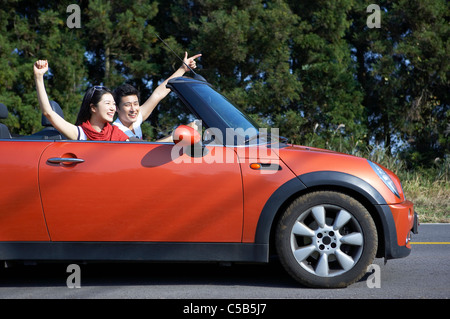 Side view of young couple riding in convertible car, - Stock Photo