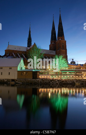 Reflection of Uppsala Cathedral in still water against clear blue sky at dusk - Stock Photo